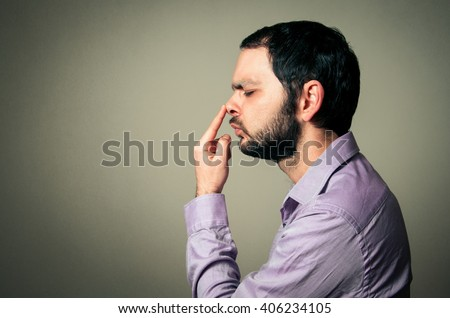 man with beard touching his nose - stock photo