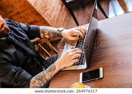 Man with beard working on laptom in a cafe.