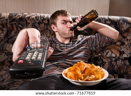 Man with beer and chips watching TV at home - stock photo