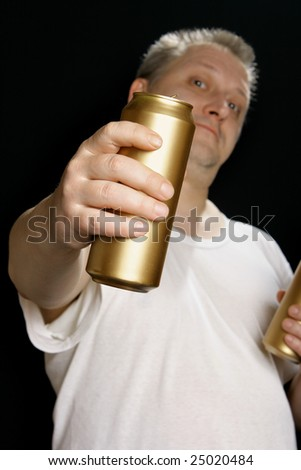 Man with beer can over black background. Focus on the can! - stock photo