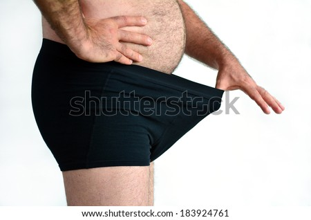 Man with belly looking down his underwear against white background with copy space. Concept photo of male sexuality and man sex problems. - stock photo