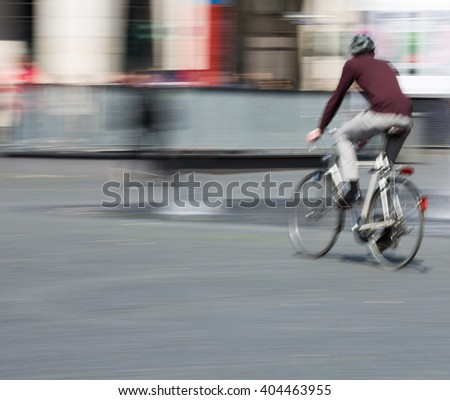 man with bicycle in the city, blurred and out of focus, moving with Copy Space - stock photo