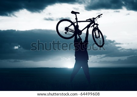 Man with bicycle lifted above him - stock photo