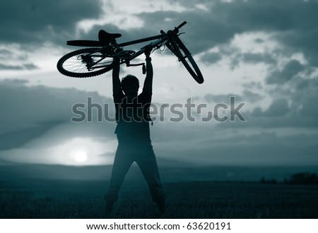 Man with bicycle lifted above him. Blue gray toned - stock photo