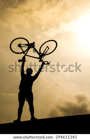 Man with bicycle lifted above him in the evening.