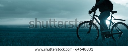 Man with bicycle standing on field on sunset background - stock photo