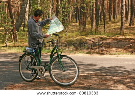 man with bicycle stopping on rural road and looking at map - stock photo