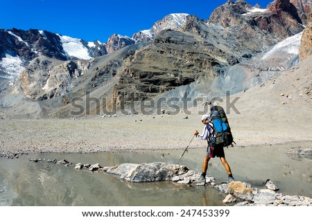 Man with big backpack resting on trekking pole moves a mountain river - stock photo
