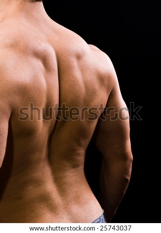 Man with big muscular back on black background - stock photo