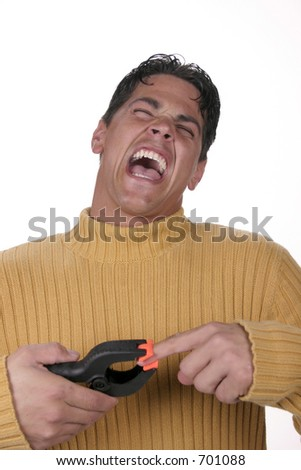 Man with big spring loaded clamp pinching his finger - stock photo
