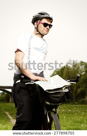Man with bike checking his way - stock photo
