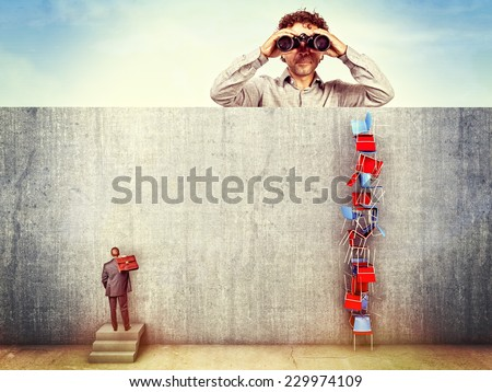 man with binoculars and worker behind the wall - stock photo