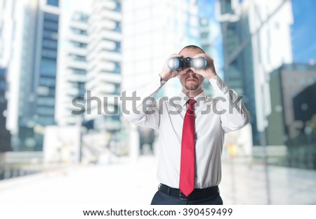 man with binoculars building background