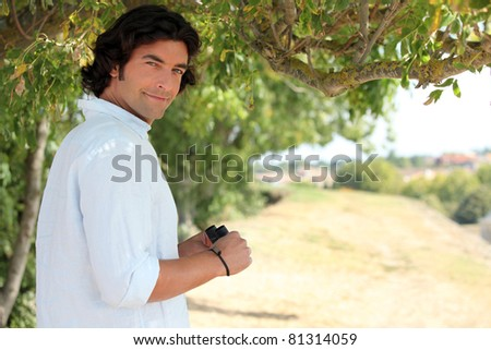 Man with binoculars in the countryside - stock photo