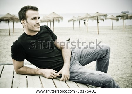man with black shirt on the beach - stock photo