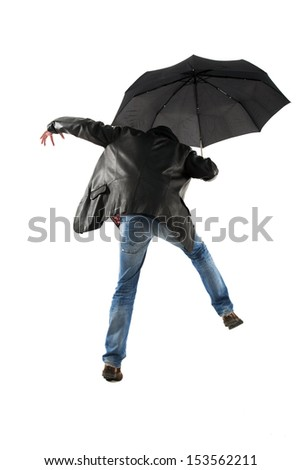 Man with black umbrella walking on a white background back to the camera - stock photo