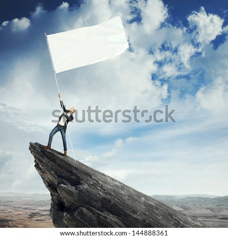 Man with blank flag standing on the top of a rock - stock photo