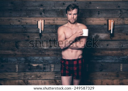 Man with blonde hair and bare chest wearing red flannel shorts. Standing against wooden wall inside wooden cabin. - stock photo