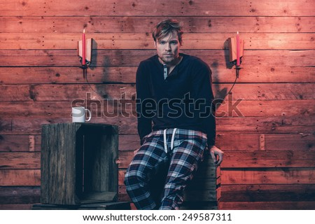 Man with blonde hair and beard wearing winter sleepwear. Sitting on wooden crate inside cabin. - stock photo