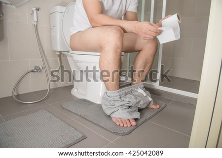 Man with book sitting on the toilet - stock photo
