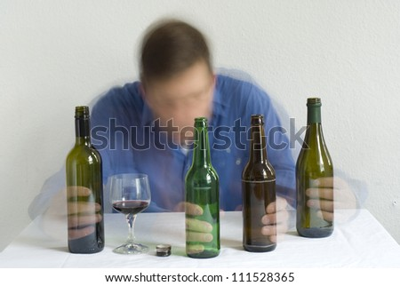 Man with bottles on the table. Blurry movement. - stock photo