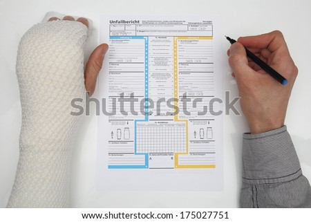 Man with bound hand fills out a accident report - stock photo