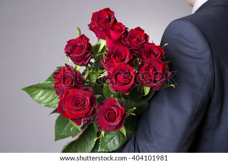 Man with bouquet of red roses on a gray background. Present at the International Women's Day