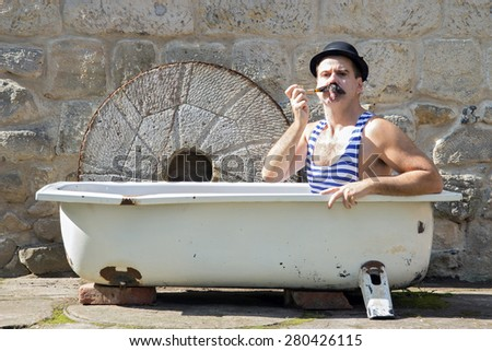 man with bowler hat smoking a pipe in the bath - stock photo