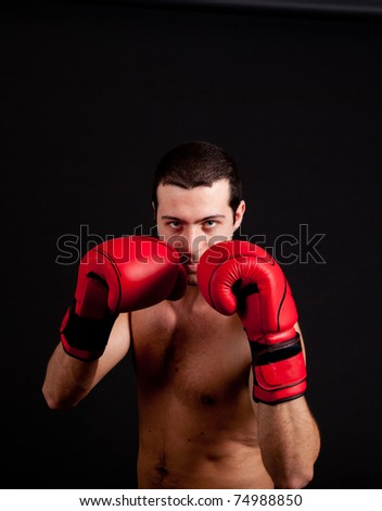 Man with boxing gloves on black background - stock photo