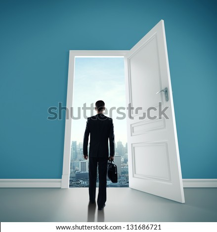 man with briefcase and open door to city - stock photo