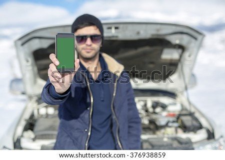 Man with broken car and smart phone, Man hand holding mobile smart phone , tablet,cellphone over Blurred of car technician. transportation, winter and vehicle concept. green screen phone. SOS - stock photo