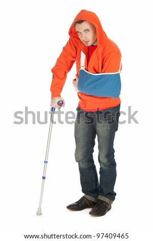 man with broken hand walking on crutch, full length, white background - stock photo