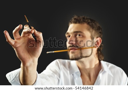 Man with brush and palette. Shallow depth-of-field - stock photo