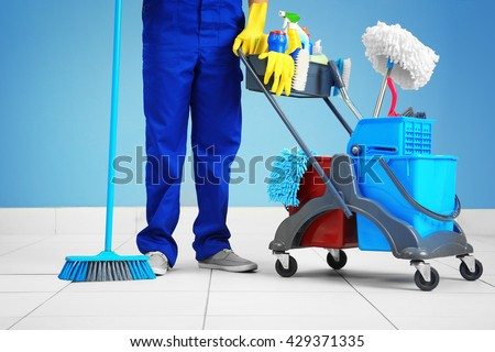 Man  with brushes and detergents on grey background - stock photo
