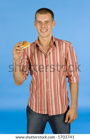 man with burger on the blue background - stock photo