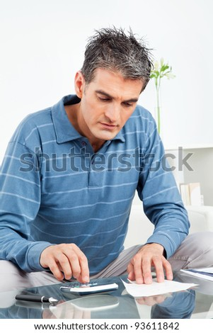 Man with calculator and bills on living room table - stock photo