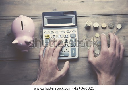 man with calculator, piggy bank and coins on wooden table - stock photo