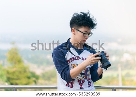 mAN with camera - Portrait of a handsome young in glasses man with camera