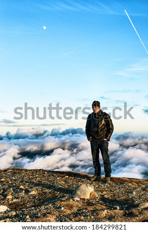 Man with camera standing at the edge of a peak over the clouds