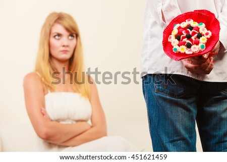 Man with candy bunch flowers behind back and pretty unhappy bored woman. Boyfriend with present gift trying to apologize girlfriend.