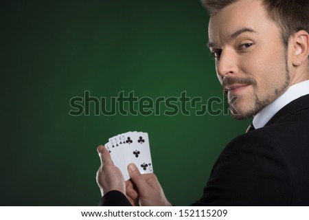 Man with cards. Cheerful young man in formalwear holding cards in his hands and looking over shoulder while isolated on green - stock photo
