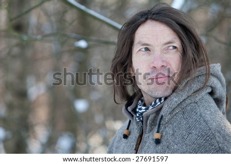 Man with characteristic face standing in a winter landscape - stock photo