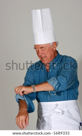 Man with chef's hat and apron rolling up his sleeves - stock photo