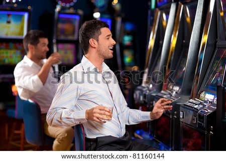 man with cigar, sitting by the slot machine, winning - stock photo