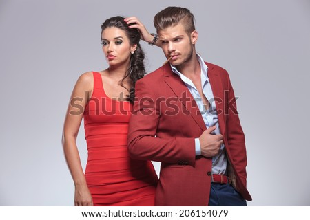 man with cigarette in his mouth near sexy woman, posing in studio looking away from the camera