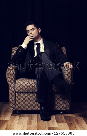 Man with cigarette sitting in vintage armchair - stock photo