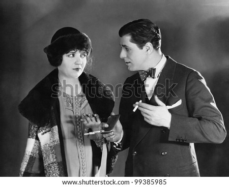 Man with cigarettes talking to woman - stock photo
