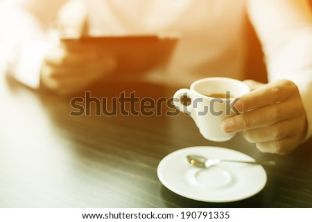 Man with coffee and tablet computer reading news at motning in cafe shop - stock photo