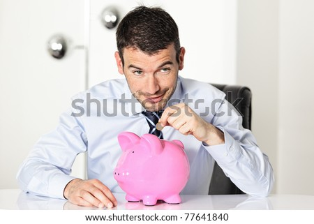 man with coin and pink piggy bank - stock photo