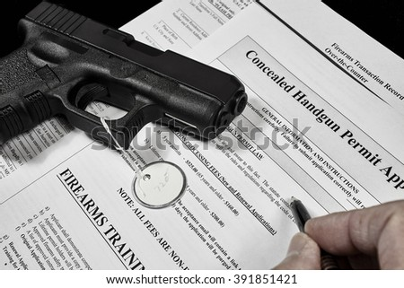 man with concealed carry permit application and pistol gun firearm - stock photo